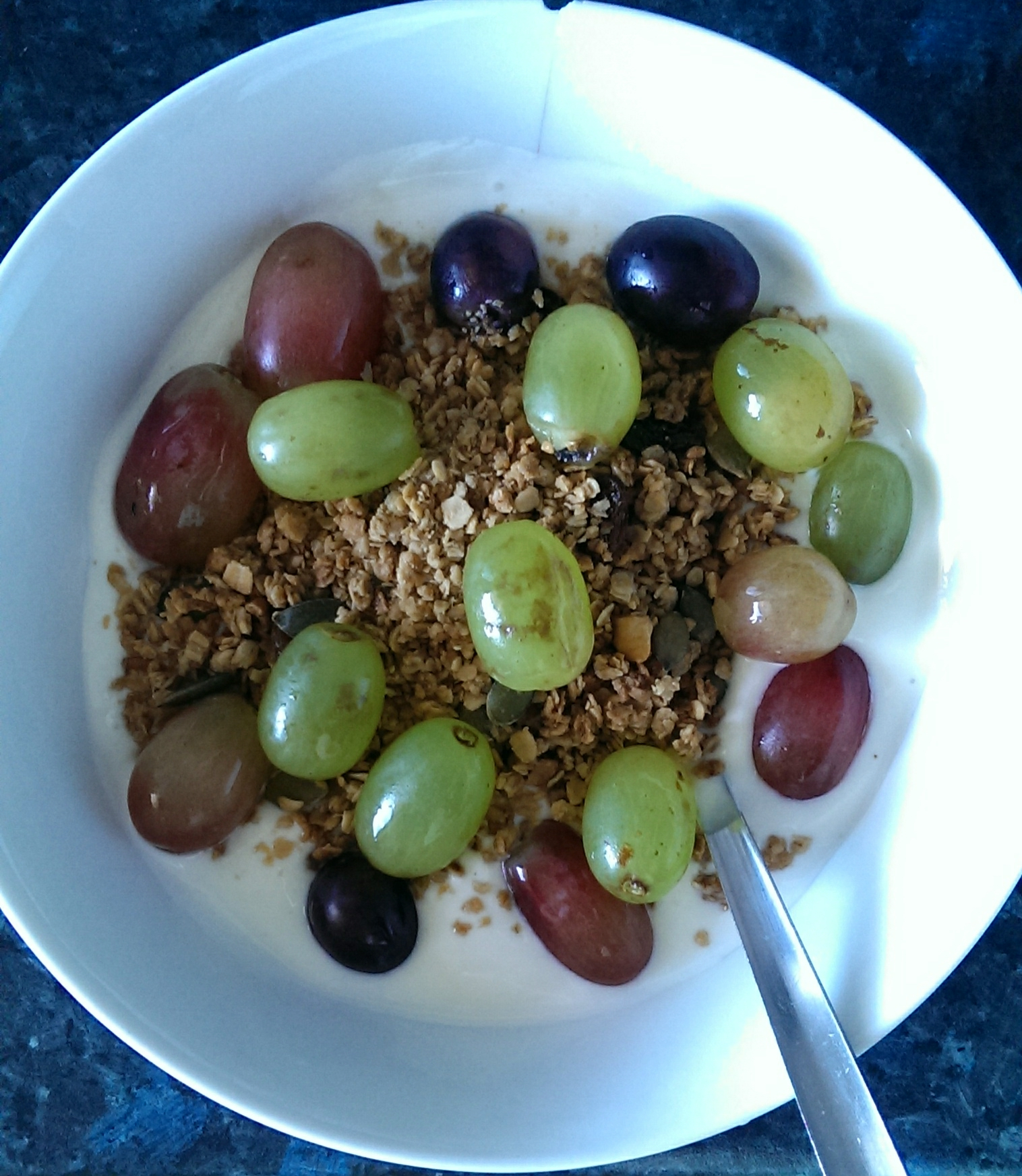 Homemade granola with  red and green grapes and natural yoghurt. Yummy!